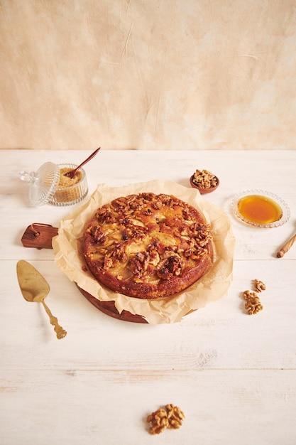 Colpo verticale di una deliziosa torta di mele e noci con miele circondato da ingredienti su un tavolo bianco Foto Gratuite