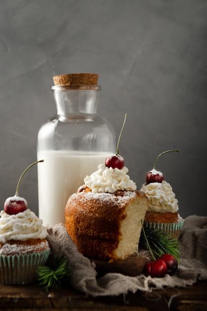 Colpo verticale di deliziosi cupcakes con zucchero a velo e ciliegina sulla torta con il latte Foto Gratuite