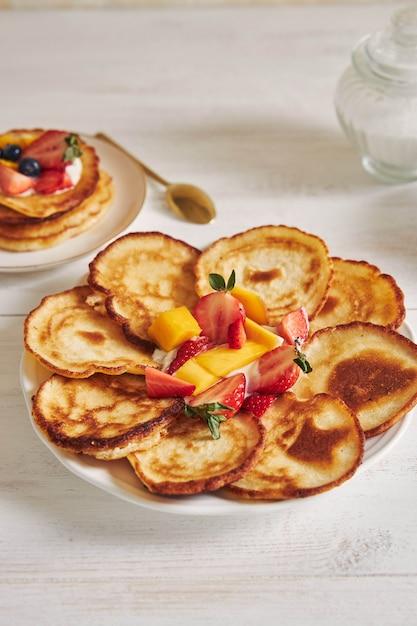 Colpo verticale di deliziose frittelle con frutta nel mezzo Foto Gratuite