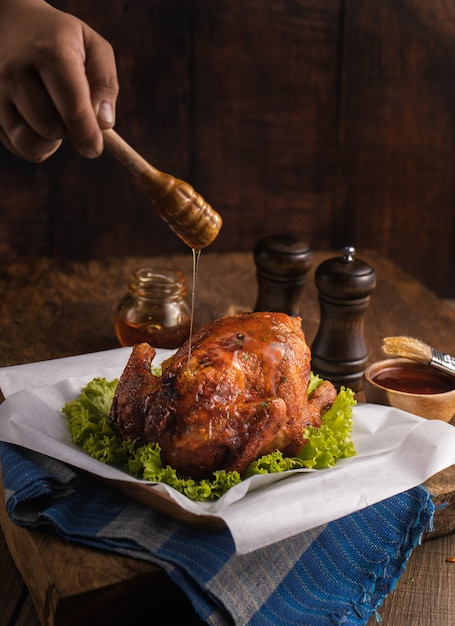 Vertical shot of a delicious roasted chicken garnished with vegetables and honey on a table Free Photo