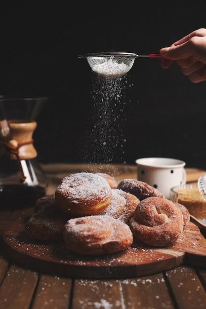 Colpo verticale di deliziose ciambelle di serpente cosparse di zucchero a velo e caffè chemex Foto Gratuite