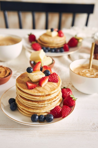 Vertical shot of delicious vegan tofu pancakes with colorful fruits, syrup  and coffee Free Photo