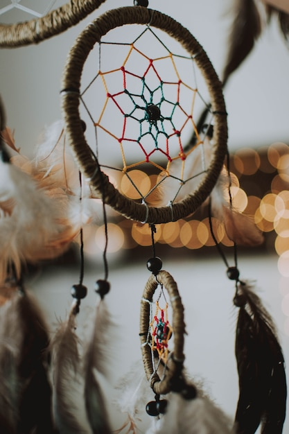 Vertical shot of a dream catcher with a blurred bokeh background Free Photo