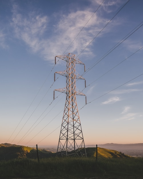 Vertical shot of an electric tower on a grassy field under a blue sky Free Photo