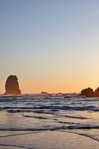 Colpo verticale del famoso haystack rock sulla costa rocciosa dell'oceano pacifico Foto Gratuite