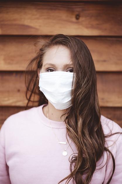 Colpo verticale di una donna che indossa una maschera sanitaria davanti a una parete in legno Foto Gratuite