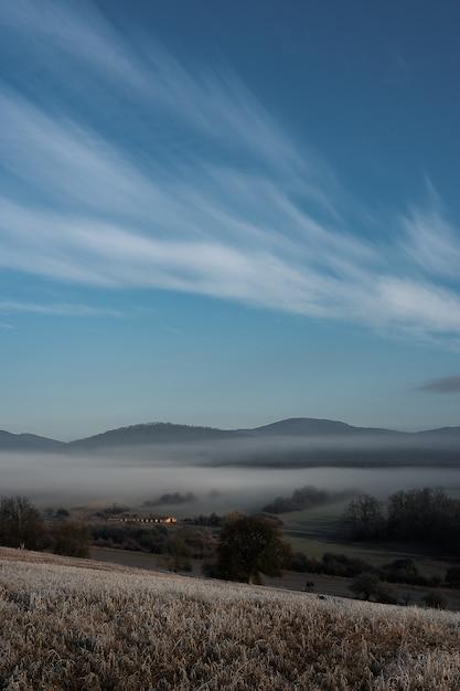 Colpo verticale di un campo nebbioso e montagne con un cielo blu sullo sfondo Foto Gratuite