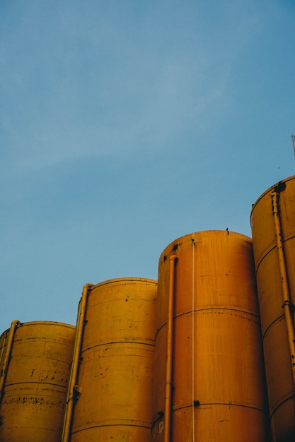 Vertical shot of four yellow metallic silos with the blue sky Free Photo