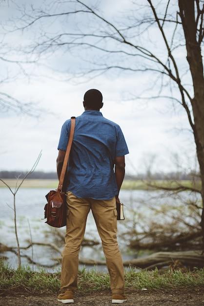 Вертикальный снимок сзади мужчины, который носит сумку и держит библию Бесплатные Фотографии