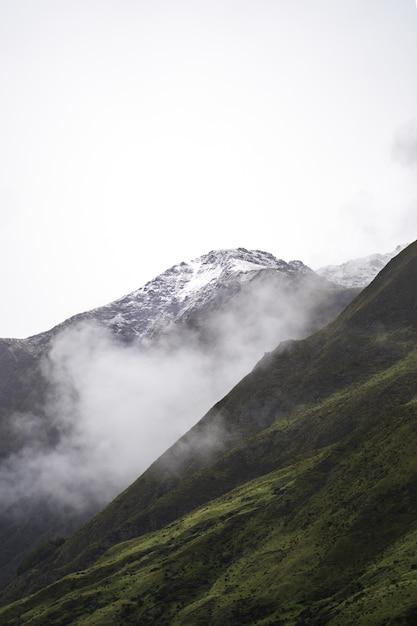 Colpo verticale delle verdi colline in una giornata uggiosa Foto Gratuite