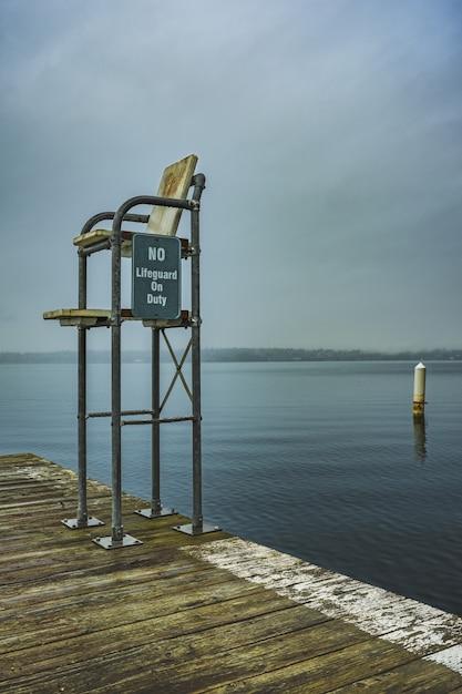 Inquadratura verticale di una stazione di bagnino sul molo con un mare aperto e un cielo cupo sullo sfondo Foto Gratuite