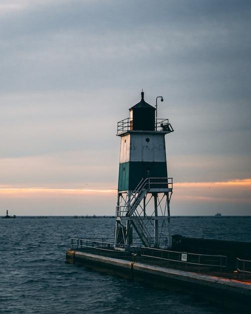 Colpo verticale di un faro e un bel tramonto Foto Gratuite