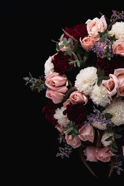 Colpo verticale di un lussuoso bouquet di rose rosa e rosse e dalie bianche su sfondo nero Foto Gratuite