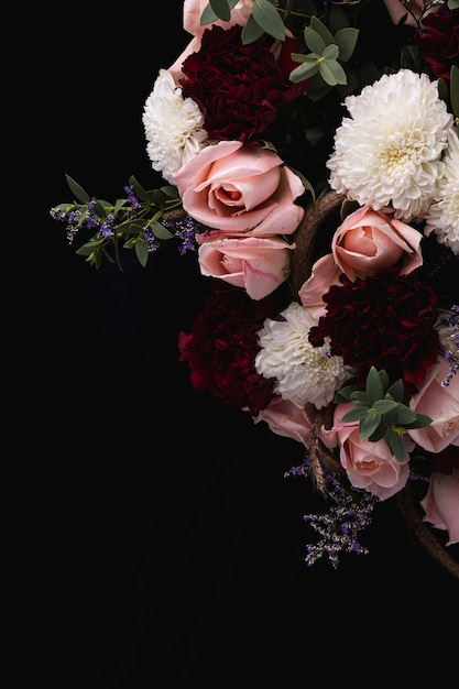 Vertical shot of a luxurious bouquet of pink roses and white, red dahlias on a black background Free Photo
