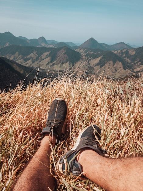 Colpo verticale dei piedi maschili e la vista sulle montagne a rio de janeiro Foto Gratuite