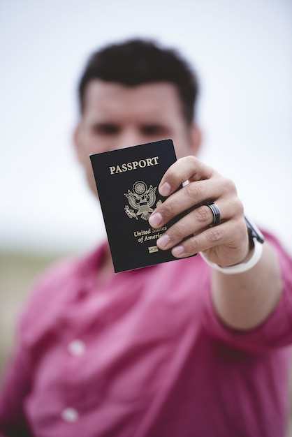Vertical shot of a male holding up his passport towards the camera with a blurred background Free Photo