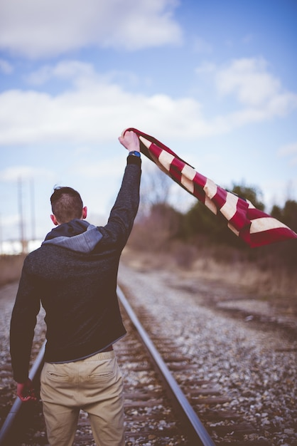 Vertical shot of a male standing on train tracks while holding up the united states flag Free Photo