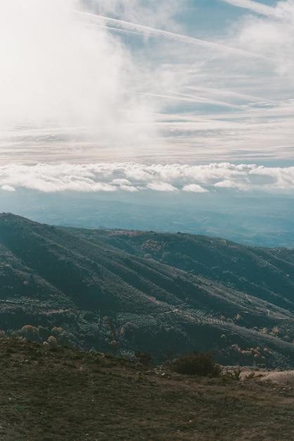Colpo verticale delle montagne sotto un cielo nuvoloso blu Foto Gratuite
