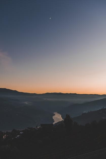Colpo verticale di montagne e un lago sotto un cielo blu Foto Gratuite
