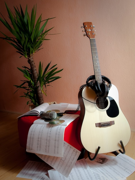Vertical shot of musical notes next to a guitar, headphones and a plant Free Photo