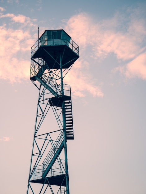 Vertical shot of an observation tower under the beautiful sunset sky Free Photo