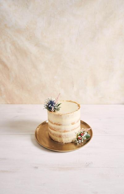 白い背景の上に花と金色のエッジを持つ美しくておいしいケーキの垂直ショット 無料写真