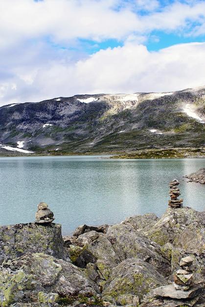ノルウェーの高いロッキー山脈に囲まれた美しい湖の垂直ショット 無料写真