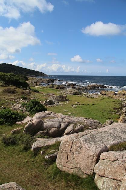 Вертикальный снимок красивого прибрежного пейзажа с большими камнями в хаммер-одде, борнхольм, дания Бесплатные Фотографии