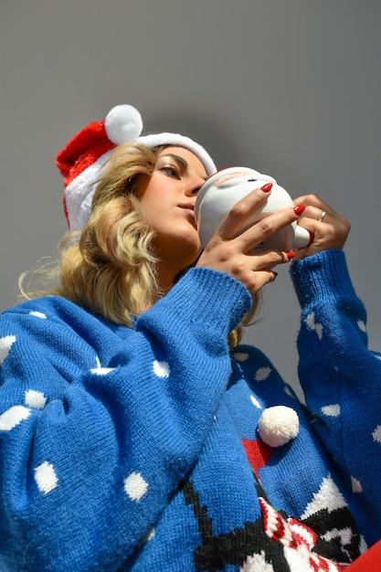 산타 컵을 들고 크리스마스 드레스와 모자를 쓰고 아름다운 젊은 아가씨의 세로 샷 무료 사진