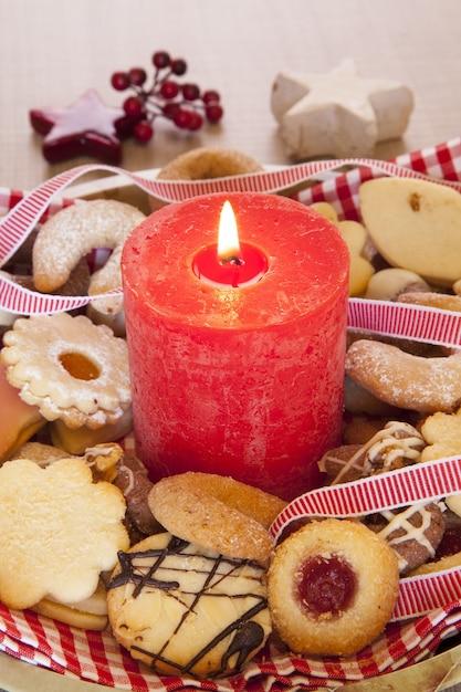 クリスマスのクッキーと装飾品と大きな赤い燃えるろうそくの垂直ショット 無料写真