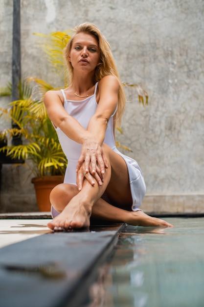 Вертикальный снимок блондинки, сидящей у бассейна Бесплатные Фотографии
