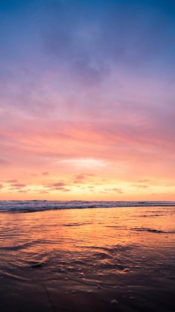 Вертикальная съемка водоема с розовым небом во время захода солнца. идеально подходит для обоев. Бесплатные Фотографии