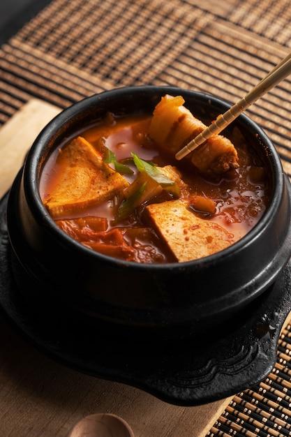 木製のテーブルの上においしい野菜とジャガイモのスープのボウルの垂直ショット 無料写真