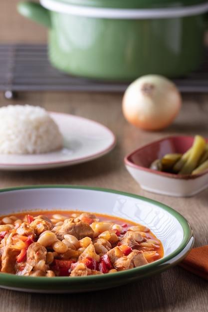야채 수프 한 그릇, 피클 한 그릇 및 나무 테이블에 쌀 한 접시의 세로 샷 무료 사진