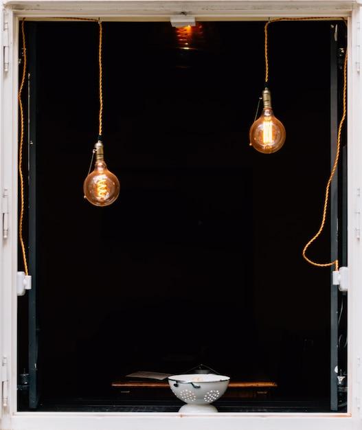ペンダントライトと黒のウィンドウ上のボウルの垂直方向のショット 無料写真