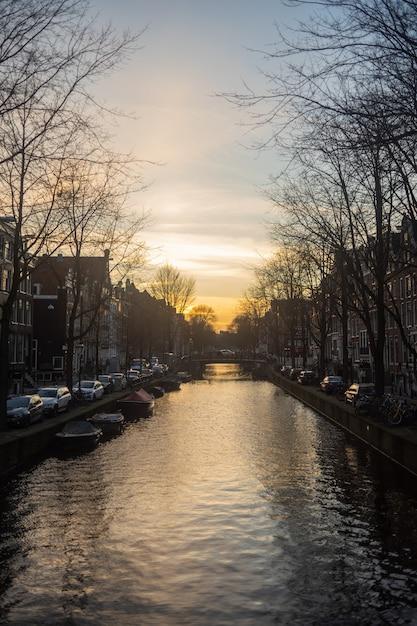 アムステルダム南東部の川に沈む夕日の垂直ショット 無料写真