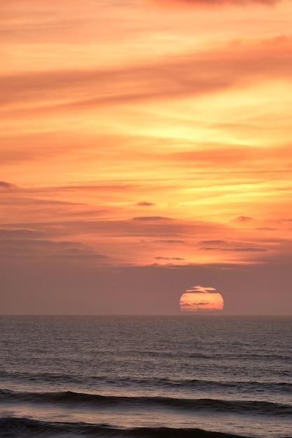 海に沈む息を呑むような夕日の風景の垂直ショット 無料写真