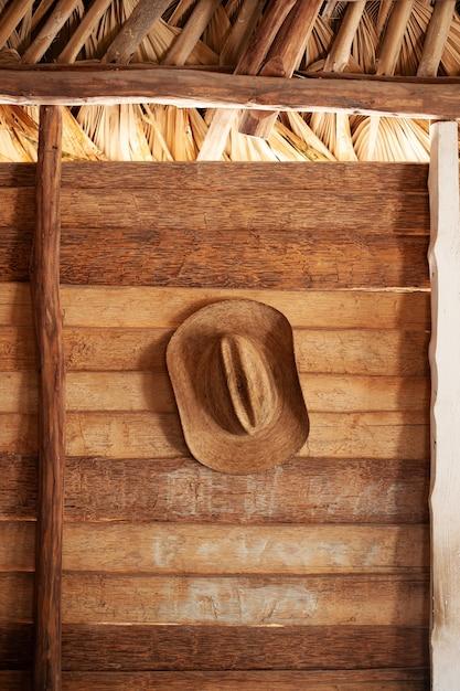 木製の壁にぶら下がっている茶色の帽子の垂直ショット 無料写真