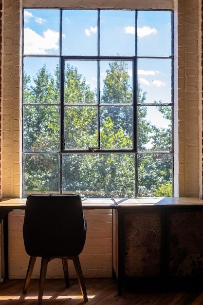 Вертикальный снимок стула и стола возле большого окна с потрясающим видом на зелень снаружи Бесплатные Фотографии