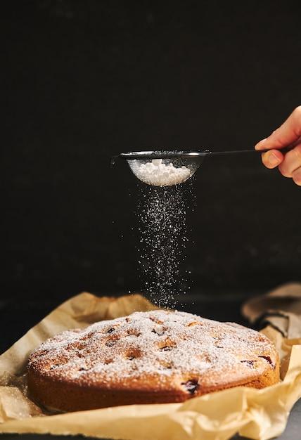 Вертикальный снимок вишневого торта с сахарной пудрой и ингредиентами сбоку на черном фоне Бесплатные Фотографии