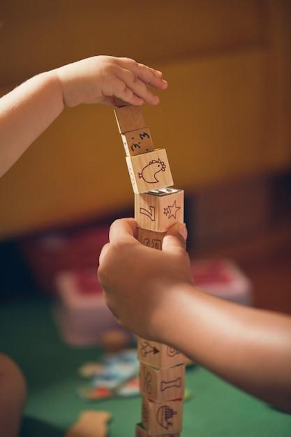 아이의 세로 샷과 바닥에 교육용 나무 큐브를 가지고 노는 성인 무료 사진