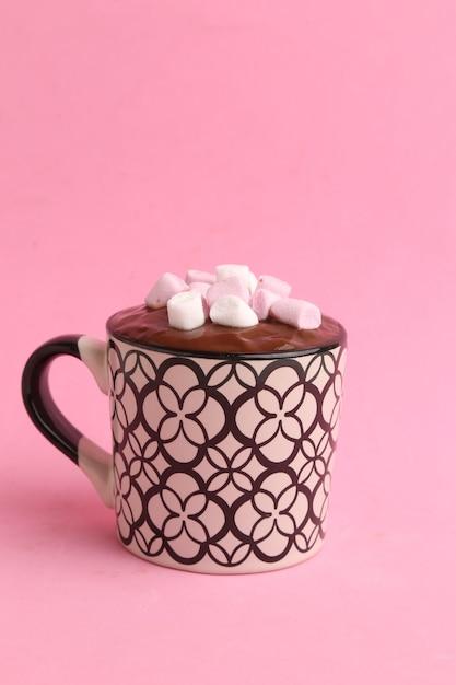 Вертикальный снимок чашки горячего шоколада с зефиром, изолированного на розовом фоне Бесплатные Фотографии