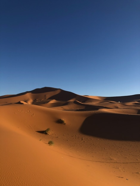 Вертикальный снимок пустыни с песчаными дюнами в солнечный день Бесплатные Фотографии