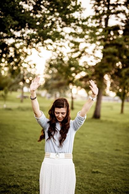 目を閉じて両手を空に向けた女性の垂直ショット 無料写真