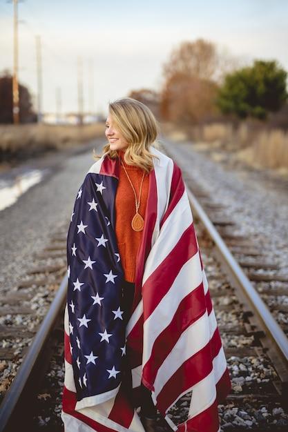 Вертикальный снимок женщины с американским флагом на плечах, стоящей на железной дороге Бесплатные Фотографии