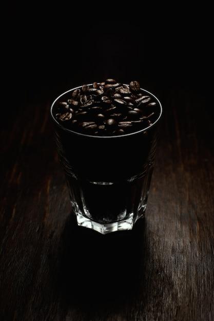 黒い背景を持つ木製の表面にコーヒー豆で満たされたガラスのコップの垂直ショット 無料写真