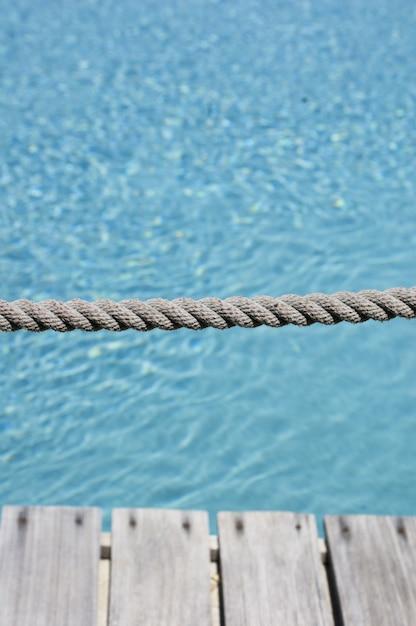 プール内の澄んだ水の背景を持つ灰色のロープの垂直方向のショット 無料写真