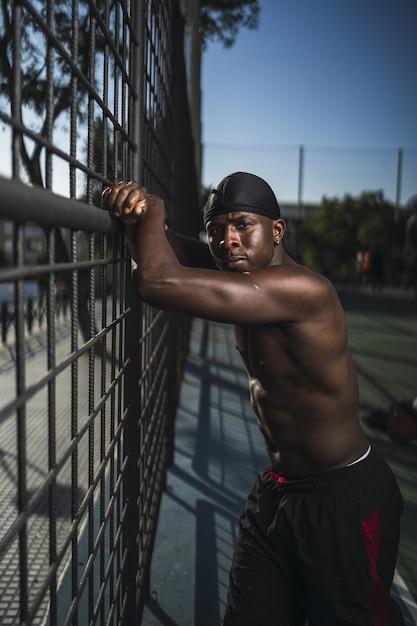 バスケットボールコートのフェンスに寄りかかっている半裸のアフリカ系アメリカ人男性の垂直ショット 無料写真