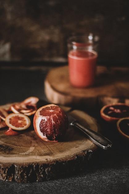 丸い木製のスラブのナイフの近く半分皮をむいたブラッドオレンジの垂直ショット 無料写真