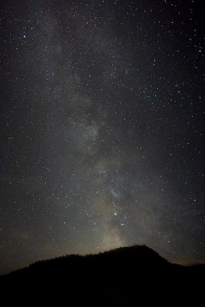 은하수의 숨막히는 풍경이있는 언덕의 세로 샷 무료 사진